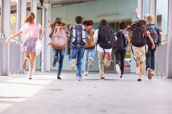 children with backpacks running