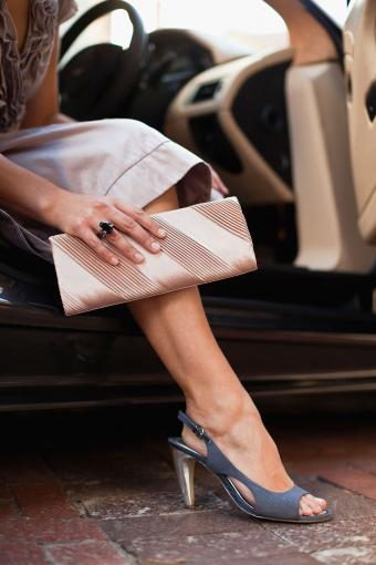 Close-up of woman holding gold clutch