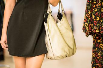 Woman holding a tan handbag