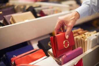 Senior woman picking up a red wallet from a rack in a bags and wallets store