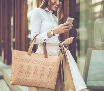 Woman shopping with tote while using smart phone