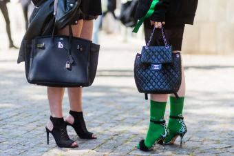 women wearing an Hermes bag and a Chanel bag and heels