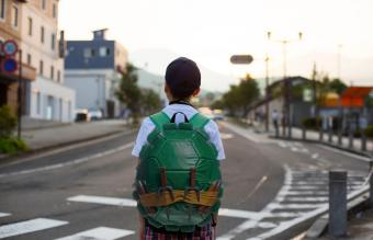 Kid with turtle shell backpack
