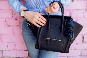 Close up black leather bag in woman's hands