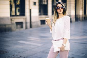 Young businesswoman carrying a white handbag and coffee