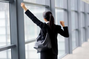 Businesswoman stretching arms while caring a charcoal purse