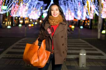 Woman in brown coat carrying a saddle tan leather bag