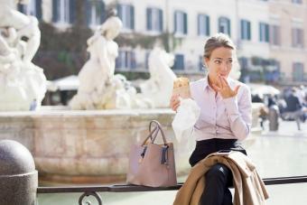 Businesswoman sitting next to beige purse on her lunch break