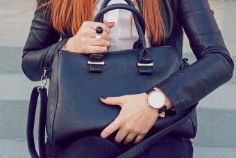 woman holding big black handbag