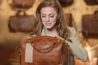 Woman in shop looking at leather bag