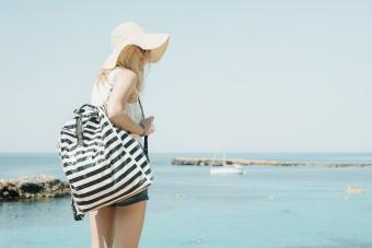 Woman with striped backpack by sea wearing a sunhat