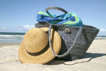 Straw hat lies on white-sand beach beside blue straw bag