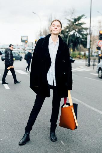 Laura Kampman wears an all black outfit with a white shirt and carries a Celine twisted cabas bag
