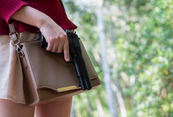Young Woman Putting A Gun In Her Handbag