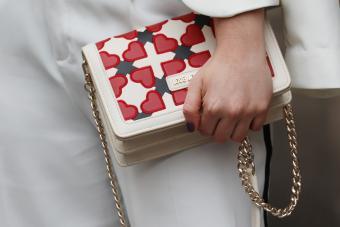 A fashionista wears a Love Moschino handbag during the Autumn/Winter 2019 London Fashion Week - Getty Editorial Use