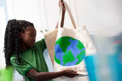 Young girl holding reusable tote bag