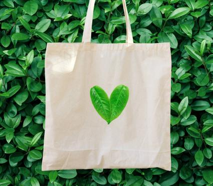 Cotton tote bag with green foliage background