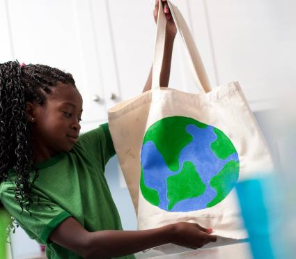 Young girl holding reusable shopping bag