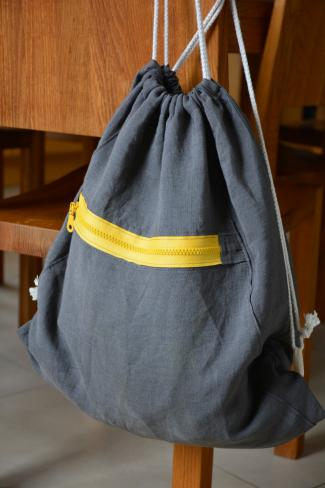 Drawstring purse suspended on back of chair