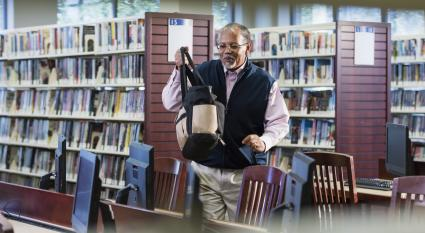 Senior man carrying a tote bag in library