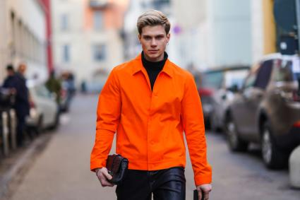 Man in orange jacket with black clutch purse