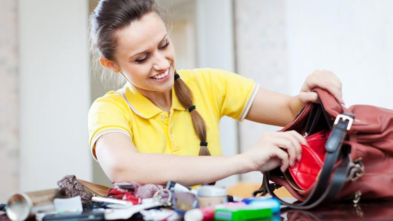 Young woman looking for something in cluttered handbag