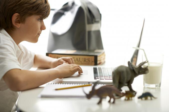 Kid doing his homework surrounded by dinosaurs