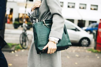 Businesswoman with green handbag standing in city
