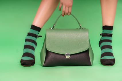Green and black handbag on a green background