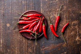 Plate of cayenne peppers/capsicum on table