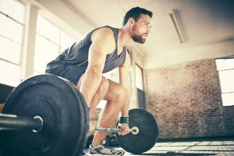 Man dead lifting barbell in gym
