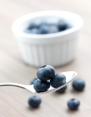 A Spoonful of Bilberries with Bowl in Background