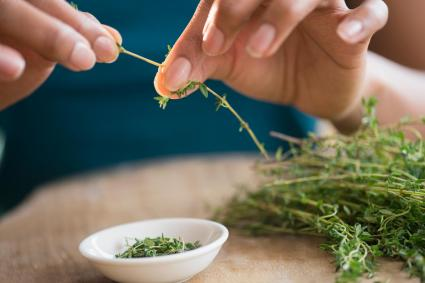 Picking leaves off thyme sprigs