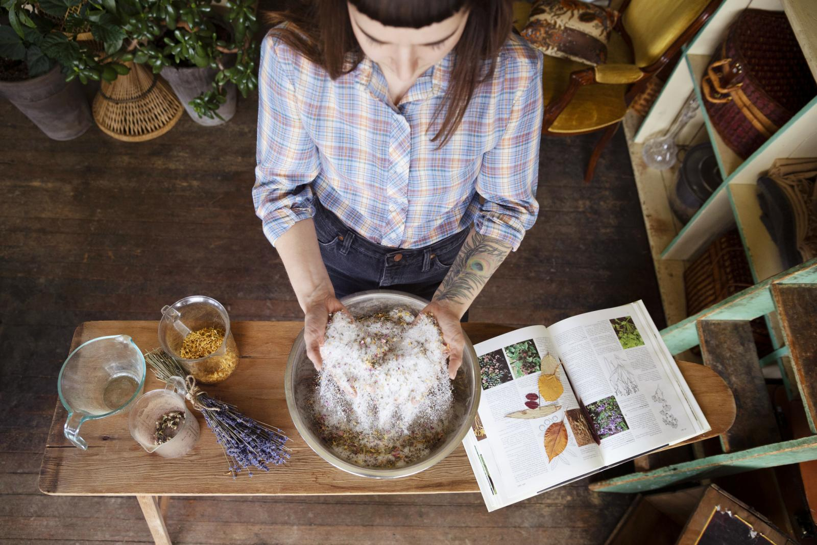 Female business owner mixing herbs and dried flowers in apothecary shop