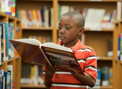 African American boy reading in library