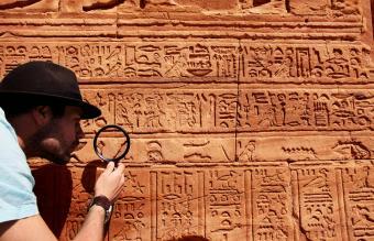 Archeologist reading hieroglyphics