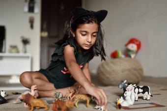 girl lining up animal toys
