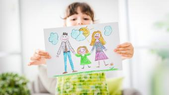 Girl holding a drawing of her family