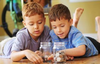 Little boy adding coins to jar