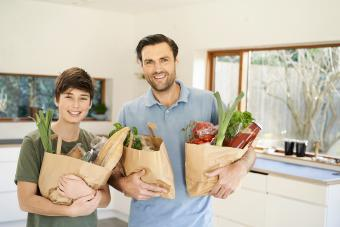 Boy and his father in kitchen holding grocery bags