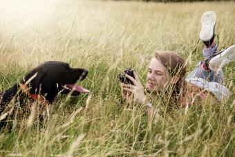 Teenager takes photos of her Labrador retriever dog in park