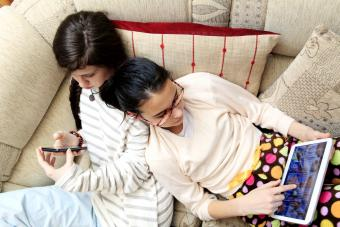 Two girls playing with gadgets