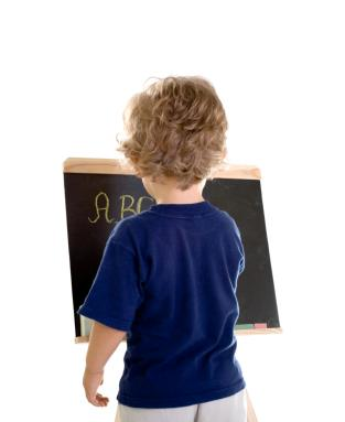 Child writing ABCs on blackboard
