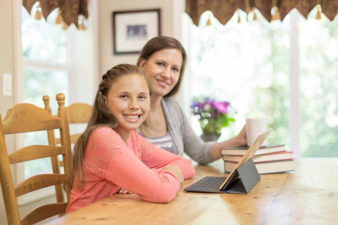 Mother homeschooling daughter at dining table