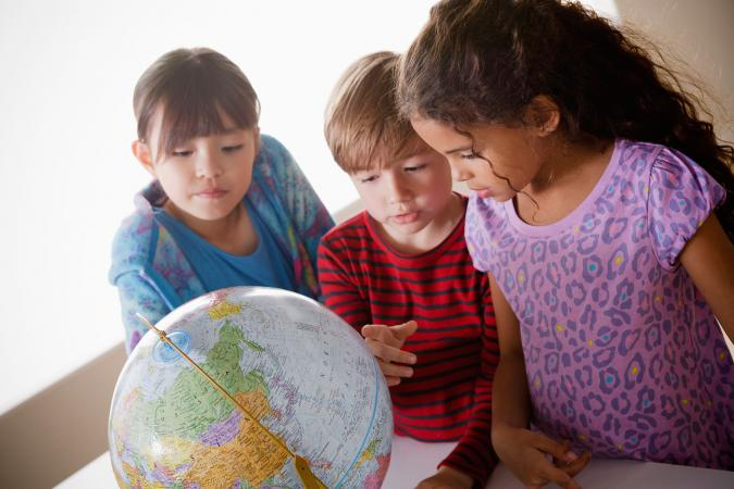 Kids studying continents on globe