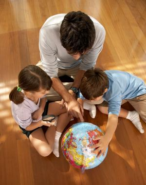 Father with children studying globe