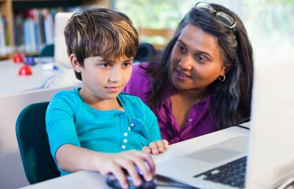 Teacher helping student using laptop