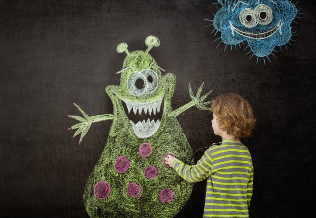 Little boy drawing a virus on blackboard