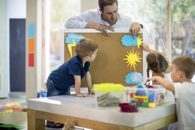 Teacher teaching weather to children