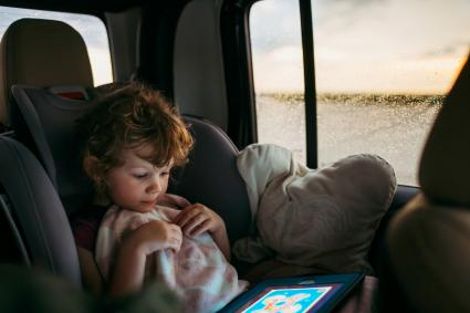 Little girl playing a game on a tablet on a car
